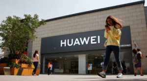 A woman looks at her phone as she walks past a Huawei shop in Beijing